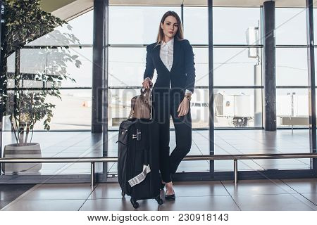 Full-length Portrait Of Confident Young Business Traveler Wearing Formal Suit Standing With Heavy Ro