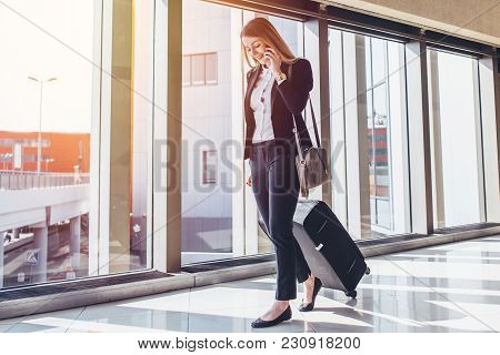 Smiling Female Passenger Proceeding To Exit Gate Pulling Suitcase Through Airport Concourse While Ta