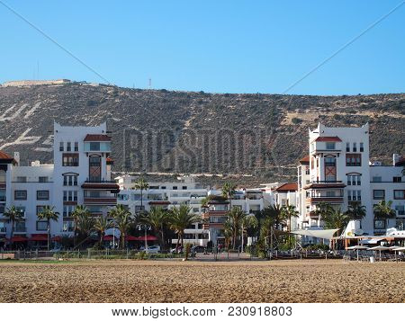 Agadir, Morocco Africa On February 2017: Beach At Seaside In Travel City With White Modern Hotel Bui