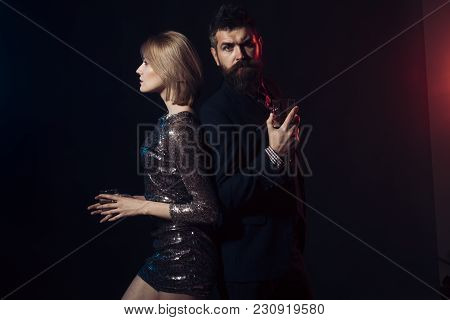 Man And Woman In Fancy Clothes Drink Wiskey On Dark Background. Corporate Party Concept. Couple Cele