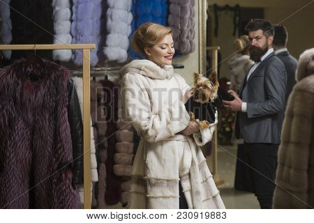 Woman In White Fur Coat With Dog And Bearded Macho Looking For New Overcoat. Girl With Cunning Face