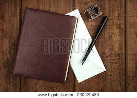 An Overhead Photo Of A Leather Bound Journal, A Blue Envelope, An Ink Well And Pen, Shot From Above