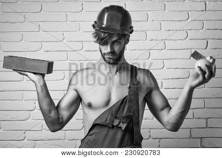 young handsome bearded macho man builder with sexy muscular athletic strong body has strong hands in orange hard hat or helmet holds pig dollar moneybox and brick on white wall background poster