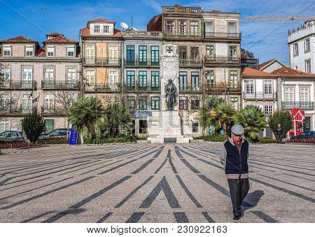 Porto, Portugal - December 8, 2016: Man Walks At Square Of Carlos Alberto With A Monument For Victim