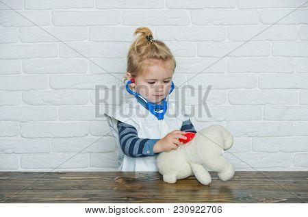Child Play Doctor With Teddy Bear On White Wall. Baby Veterinarian Examine Toy Animal With Stethosco