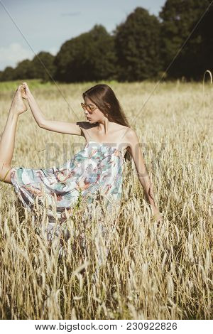 Woman In Sunglasses With Long Brunette Hair On Sunny Day, Vacation. Young Woman In Wheat Field, Agri