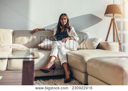Portrait Of Businesswoman Sitting On Sofa Relaxing After Work At Home.