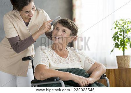 Volunteer Combing Odler Patient's Hair