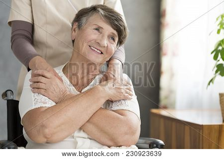 Happy Grandmother Supported By Nurse