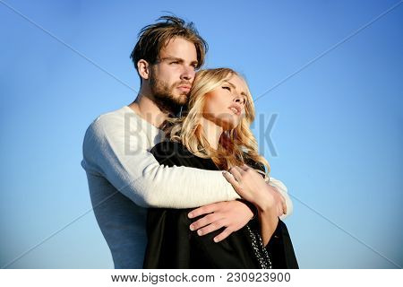 Muscular Man And Woman With Long Blond Hair, Love. Couple In Love On Blue Sky Background. Relations