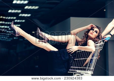 Sensual Woman Sit In Shopping Cart. Girl In Fashionable Dress, Shoes In Trolley In Shop. Fashion, Be