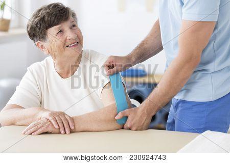 Physiotherapist Sticking Kinesiotape To Woman