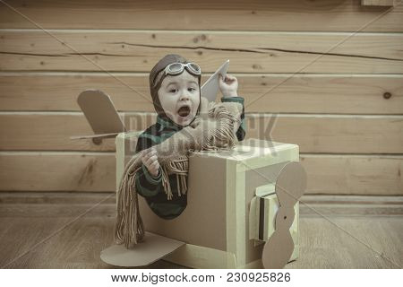Boy Wearing Old-fashioned Aviator Hat, Scarf And Goggles Flying A Cardboard Airplane In His Imaginat