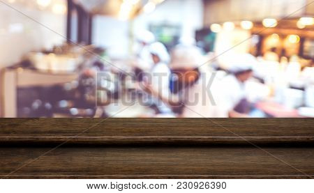 Empty Step Dark Wood Table Top Food Stand With Blur Chef Cooking At Cafe Restaurant Background Bokeh