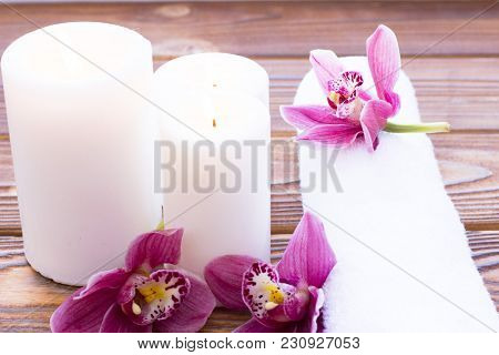 Spa And Wellness Setting With Orchid, Towel And Candle On Wooden Dark Background Closeup