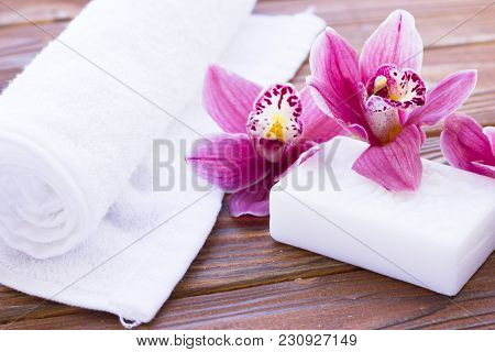 Spa And Wellness Setting With Orchid, Towel And Soap On Wooden Dark Background Closeup