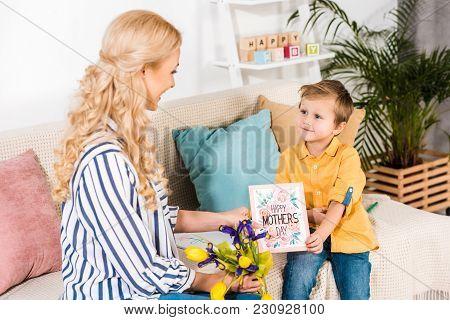 Son Gifting Mother Bouquet And Postcard On Mothers Day