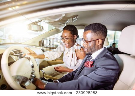 Happy Beautiful African Couple Is Choosing New Car At Dealership.