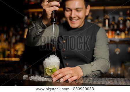 Smiling Barman Pouring Sweet Syrup Into The Fresh Sour Mojito Cocktail On The Bar Counter