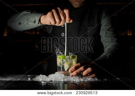 Barman Squeezing Juice From Fresh Lime In A Glass Using A Citrus Press And Splashing It Out Making A