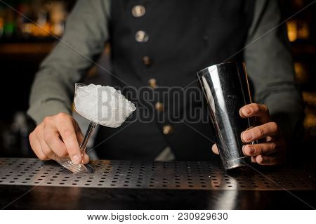 Barman Hands Holding A Shaker And A Cocktail Glass Filled With Ice On The Bar Counter