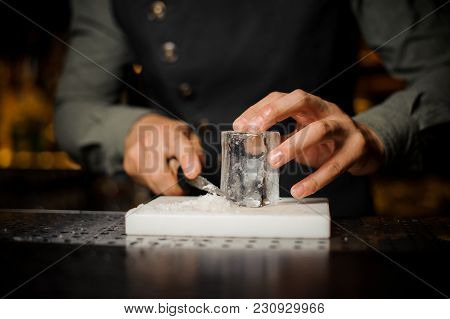 Bartender Preparing A Large Rectangular Piece Of Ice For Making Cocktail On The Bar Counter Among Ba