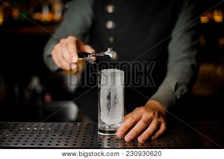 Bartender Putting A Big Rectangular Piece Of Ice Into A Cocktail Glass For Making A Tasty Alcoholic