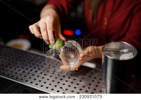 Female Barman Hands Rubbing A Cocktail Glass With Fresh Green Lime Juice On The Bar Counter
