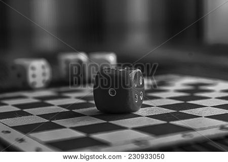 Monochrome Plastic Dice, One Red Dice On Wooden Board Background. Six Sides Cube With Black Dots. Nu
