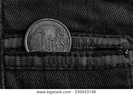 Monochrome Euro Coin With A Denomination Of 2 Euro In The Pocket Of Warn Blue Denim Jeans With Red L
