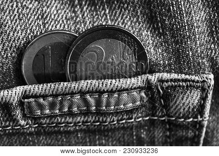Monochrome Two Euro Coins With A Denomination Of 1 And 2 Euro In The Pocket Of Worn Blue Denim Jeans