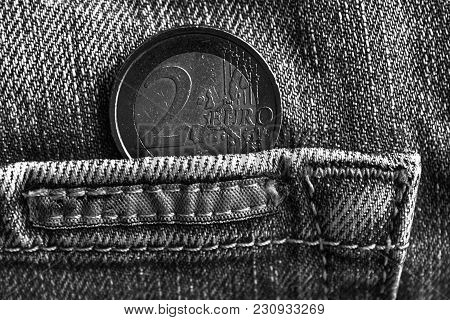 Monochrome Euro Coin With A Denomination Of 2 Euro In The Pocket Of Worn Old Blue Denim Jeans With O