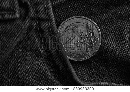 Monochrome Euro Coin With A Denomination Of Two Euro In The Pocket Of Old Vintage Blue Denim Jeans.