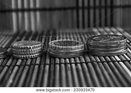 Pile Of Euro Coins, Like A Tower Lies On Wooden Bamboo Table Background