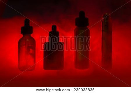 E Cigarette With Three E-liquid In The Smoke On A Dark Colour Ba