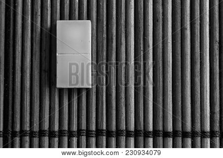 Monochrome Domino Piece On The Bamboo Brown Wooden Table Background. Domino Set Empty Dot.
