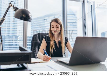 Female Chief Executive Sitting At Her Desk Taking Notes In Datebook Writing With Pen And Using Her C
