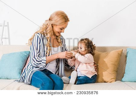 Happy Mother Feeding Adorable Little Daughter With Milk In Bottle At Home