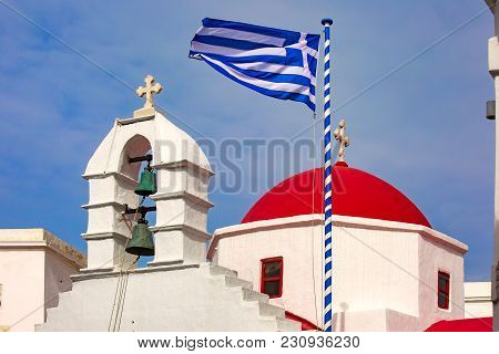 Agia Kyriaki Church, Typical Greek Church White Building With Red Dome And Large Waving Greek Flag A