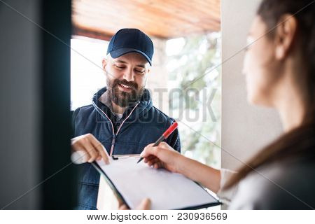 Unrecognizable Woman Receiving Parcel From Delivery Man At The Door - Courier Service Concept.