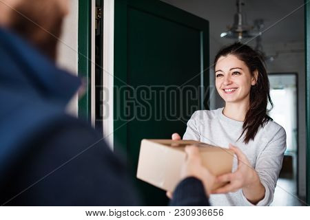 Woman Receiving Parcel From Unrecognizable Delivery Man At The Door - Courier Service Concept.