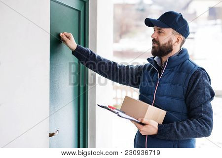 Delivery Man Delivering Parcel Box To Recipient - Courier Service Concept. A Man Knocking On The Doo