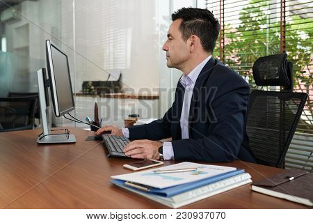 Entrepreneur Answering E-mails On His Computer In Office