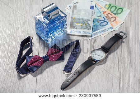 Man Perfume, Watch With A Black Leather Strap, Bow Tie And Euro Bills On Grey Wooden Background. Men