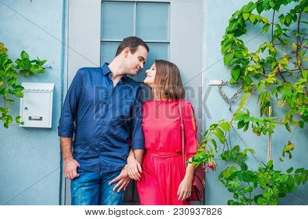 Young Romantic Married Couple In Bright Clothes Standing Near Their New Home House Door. Outdoor Vie
