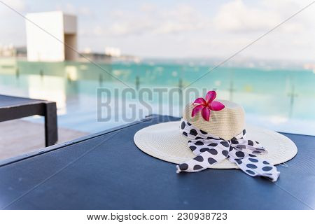 Straw Sun Hat And Frangipani Flower On The Bed Of Swimming Pool.
