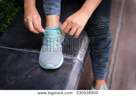 Close Up Portrait Of Woman  Tying Her Shoes Preparing For Outdoor Running.