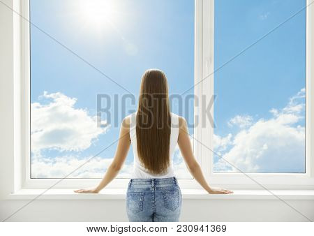 Window And Woman, Back View Of Young Girl Standing In White Home Interior, Human Looking Through Pvc