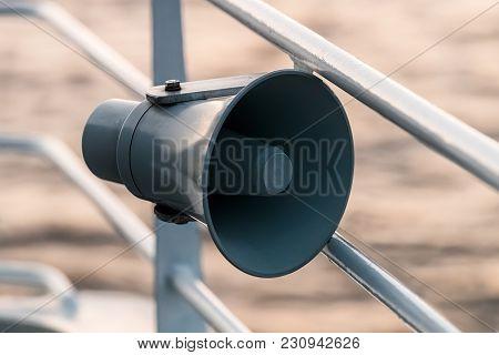 Loudspeaker On Ship's Guardrail Against Sea Background.