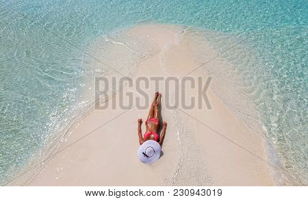Attractive Girl With A Pink Bikini And A White Hat Tanning On A Sandbank In The Maldives